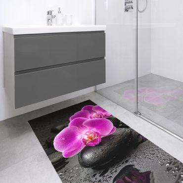 Tappeti in vinile - Fioritura di orchidee rosa su pietre con gocce - Verticale 1:2