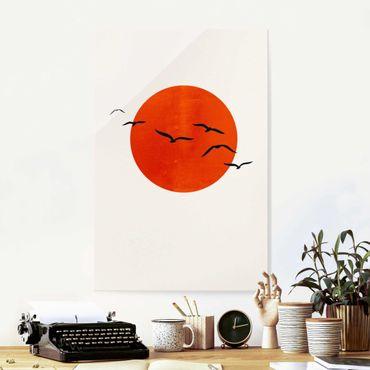 Quadro in vetro - Stormo di uccelli davanti al sole rosso - Verticale 3:2
