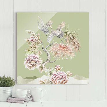 Quadro in vetro - Acquerello di cicogne in volo con fiori su verde