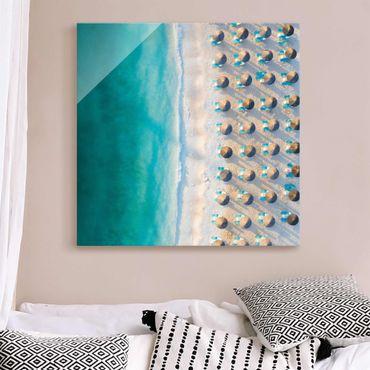 Quadro in vetro - Spiaggia sabbiosa bianca con ombrelloni di paglia